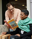 A white man showing a black girl a book