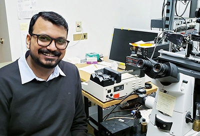 Dr. Abhishek Shrivastava seated next to a microscope.