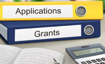 "binders labeled ""Applications"" and ""Grants"" on a table with a calculator, pen and notebook"