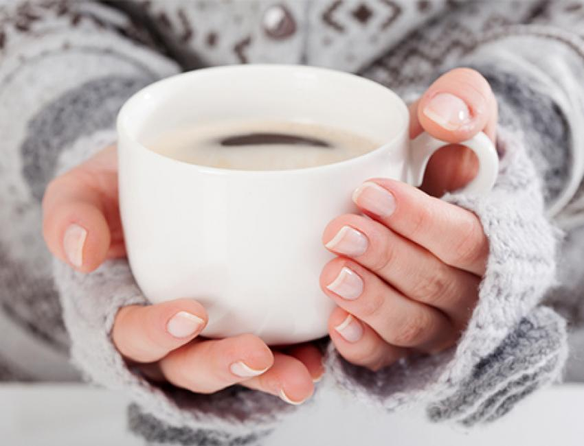 Close-up, woman's hand dressed for winter holding cup of coffee.