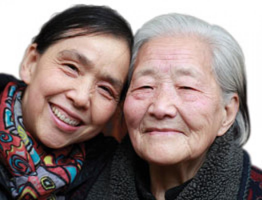 Middle aged woman and older woman smiling.