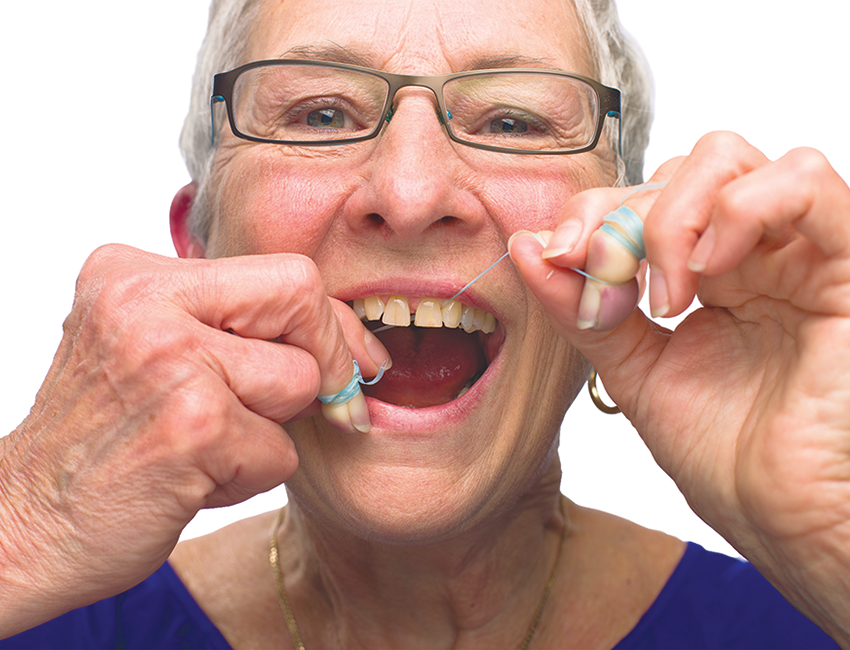 Ease the floss gently between the teeth until it reaches the gumline.