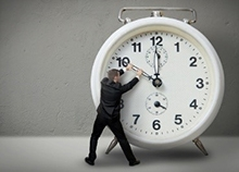 Person turning hands on over-sized clock
