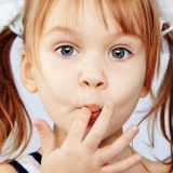 Young girl with finger in mouth