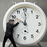Person trying to turn back time on a clock